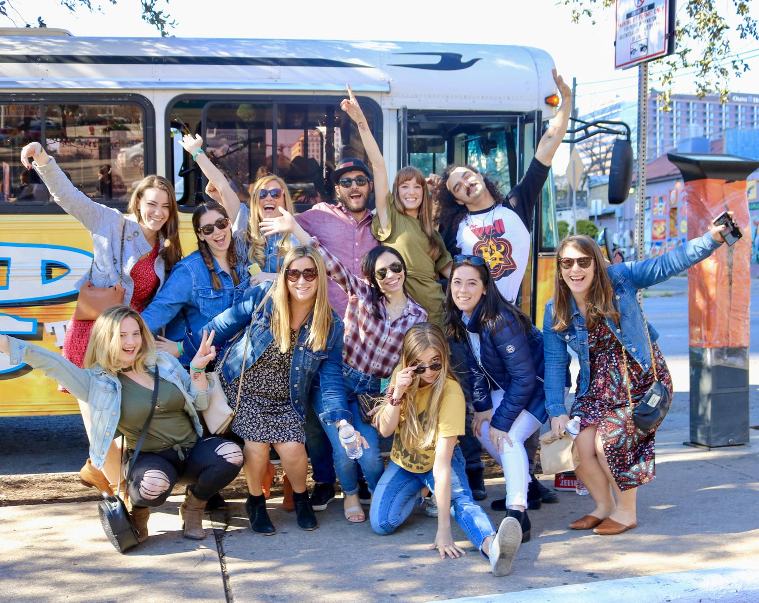 Group of friends strike a silly and festive pose in front of a decorated school bus
