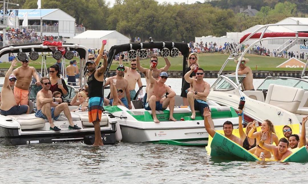 large group of people spread across 3 light boats either raising a drink or waving at the camera